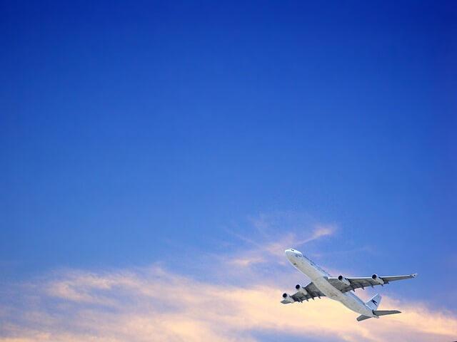 大空を飛ぶ飛行機の写真。石垣島へはどう飛んで行けばいいのか。