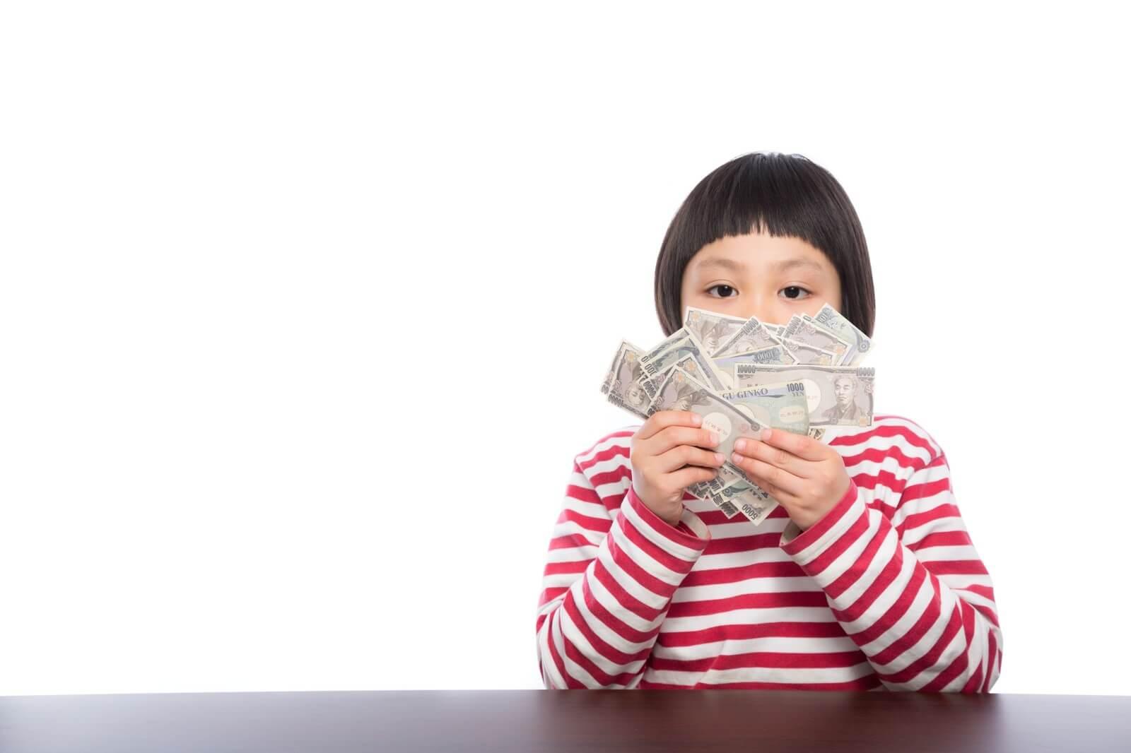 お金を両手に持つ女の子