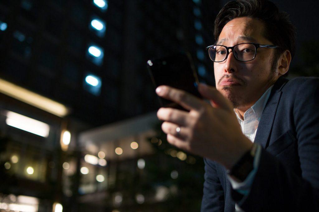 携帯を開いてうっかり顔をする男性