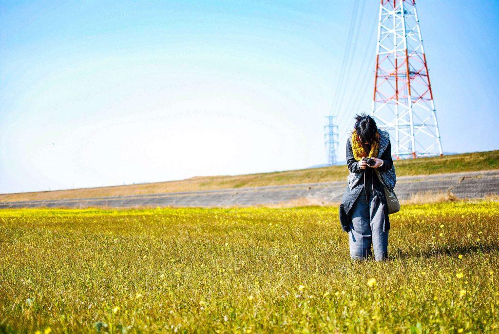 菜の花畑とカメラを構えた妻