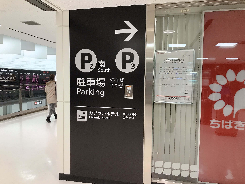 成田空港第二ターミナル2階、「駐車場」表示の看板についている「カプセルホテル」表記